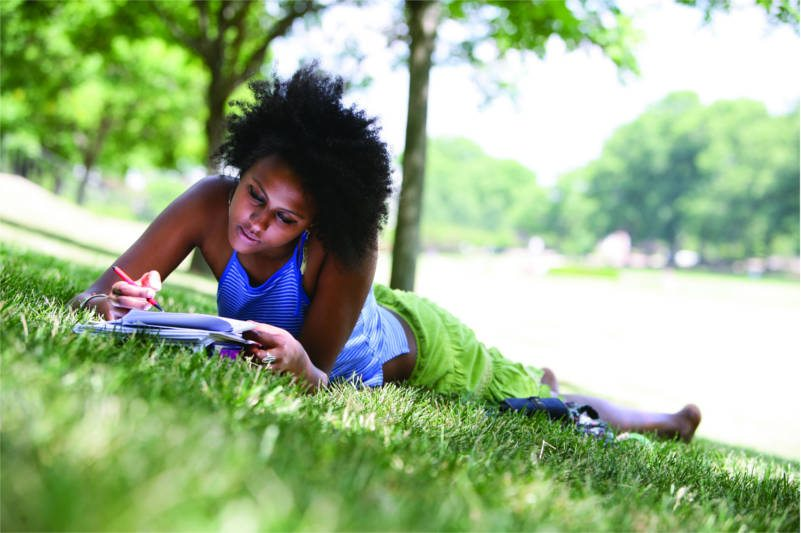 UMD student studying in the grass